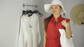 Όμορφο κορίτσι που δοκιμάζει τη νέα τσάντα κοντά στον καθρέφτη στο δωμάτιο συναρμολογήσεων Νέα γυναίκα που φορά το αστείο καπέλο  απόθεμα βίντεο