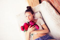 Όμορφο κορίτσι που εναπόκειται σε μια ανθοδέσμη των λουλουδιών Στοκ Φωτογραφίες