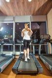 Όμορφο κορίτσι που επιλύει treadmill στη γυμναστική Στοκ εικόνες με δικαίωμα ελεύθερης χρήσης