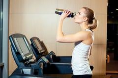 Όμορφο κορίτσι που επιλύει treadmill στη γυμναστική Στοκ Φωτογραφία