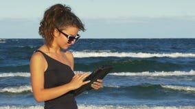 Όμορφο κορίτσι που εργάζεται στο PC ταμπλετών της θαλασσίως απόθεμα βίντεο