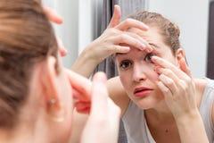 Όμορφο κορίτσι που εφαρμόζει ή που αφαιρεί έναν φακό επαφής με τον καθρέφτη Στοκ εικόνες με δικαίωμα ελεύθερης χρήσης