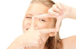 Όμορφο κορίτσι που δημιουργεί ένα πλαίσιο με τα δάχτυλα Στοκ Εικόνες