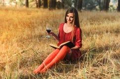 Όμορφο κορίτσι που διαβάζει ένα βιβλίο με ένα ποτήρι του κρασιού Στοκ Φωτογραφία