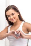 Όμορφο κορίτσι που διαμορφώνει την καρδιά με τα χέρια της Στοκ Φωτογραφία