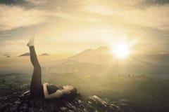 Όμορφο κορίτσι που κάνει μια άσκηση στον απότομο βράχο Στοκ Φωτογραφίες