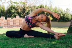Όμορφο κορίτσι που κάνει την άσκηση ευελιξίας στη χλόη Στοκ Εικόνα