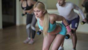 Όμορφο κορίτσι που κάνει τις ασκήσεις με τους αλτήρες απόθεμα βίντεο