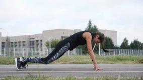 Όμορφο κορίτσι που κάνει τις διαγώνια κατάλληλα ασκήσεις, το άλμα και το χτύπημα φιλμ μικρού μήκους