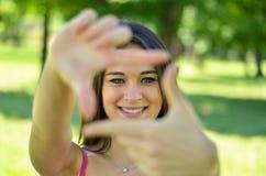 Όμορφο κορίτσι που κάνει το πλαίσιο με τα χέρια ενώ υπαίθρια Στοκ Εικόνες