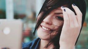 Όμορφο κορίτσι που κάνει selfies στο smartphone Μια νέα γυναίκα brunette με ένα κινητό τηλέφωνο Συσκευές και άνθρωποι Smartphone  φιλμ μικρού μήκους