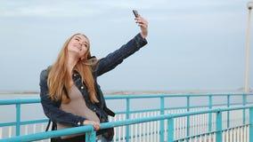 Όμορφο κορίτσι που κάνει selfies τη στάση δίπλα στον ποταμό απόθεμα βίντεο