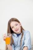 Όμορφο κορίτσι που κρατά ένα γυαλί με το χυμό από πορτοκάλι Στοκ Εικόνες