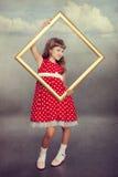 Όμορφο κορίτσι που κρατά ένα κενό πλαίσιο Στοκ Εικόνα