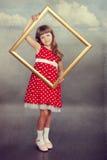 Όμορφο κορίτσι που κρατά ένα κενό πλαίσιο Στοκ Εικόνες