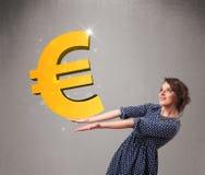 Όμορφο κορίτσι που κρατά ένα μεγάλο τρισδιάστατο χρυσό ευρο- σημάδι Στοκ Φωτογραφίες