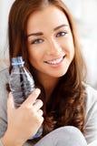 Όμορφο κορίτσι που κρατά ένα μπουκάλι νερό Στοκ Εικόνες