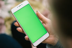 Όμορφο κορίτσι που κρατά ένα smartphone στα χέρια ενός πράσινου scre Στοκ Φωτογραφίες
