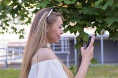 Όμορφο κορίτσι που κρατά καθιερώνοντα τη μόδα κινητό στοκ εικόνες