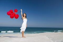 Όμορφο κορίτσι που κρατά κόκκινα ballons Στοκ Φωτογραφία