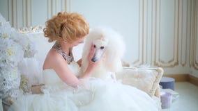 Όμορφο κορίτσι που κτυπά ένα άσπρο σκυλί απόθεμα βίντεο