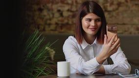 Όμορφο κορίτσι που μιλά στους συνέταιρους που χρησιμοποιούν μια κινητή τηλεφωνική κάμερα απόθεμα βίντεο