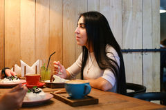 Όμορφο κορίτσι που μιλά, που ακούει, που τρώει και που χαμογελά στον πίνακα στο γ στοκ φωτογραφία