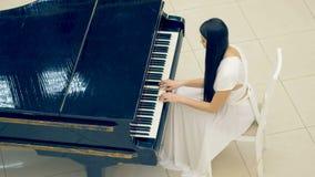 Όμορφο κορίτσι που παίζει το πιάνο στο άσπρο φόρεμα απόθεμα βίντεο