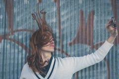 Όμορφο κορίτσι που παίρνει ένα selfie σε ένα αστικό πλαίσιο Στοκ Εικόνες