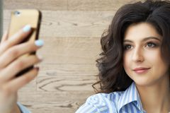 Όμορφο κορίτσι που παίρνει ένα selfie Χαριτωμένο κορίτσι brunette με τις πανέμορφες μπούκλες στο κεφάλι της που παίρνει ένα selfi Στοκ Φωτογραφία