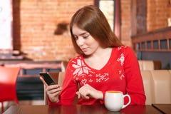 Όμορφο κορίτσι που παίρνει sms στο κινητό τηλέφωνο στον καφέ. Στοκ εικόνα με δικαίωμα ελεύθερης χρήσης