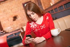 Όμορφο κορίτσι που παίρνει sms στο κινητό τηλέφωνο στον καφέ. Στοκ φωτογραφία με δικαίωμα ελεύθερης χρήσης