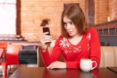 Όμορφο κορίτσι που παίρνει sms στο κινητό τηλέφωνο στον καφέ. Στοκ Εικόνες