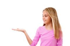 Όμορφο κορίτσι που παρουσιάζει κάτι στην παλάμη του χεριού της απομονωμένος Στοκ Φωτογραφία