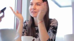 Όμορφο κορίτσι που παρουσιάζει φίλη smartphone στον καφέ απόθεμα βίντεο