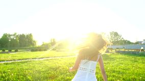 Όμορφο κορίτσι που περπατά έχοντας τη διασκέδαση στην πράσινη χλόη στη θερινή ημέρα πάρκων στο ηλιοβασίλεμα ήλιων Ευτυχία υγείας  φιλμ μικρού μήκους