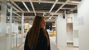 Όμορφο κορίτσι που περπατά γύρω από το κατάστημα επίπλων απόθεμα βίντεο