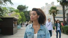 Όμορφο κορίτσι που περπατά στη μουσική πόλεων και ακούσματος φιλμ μικρού μήκους