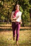 Όμορφο κορίτσι που περπατά στο πάρκο φθινοπώρου στοκ φωτογραφία