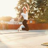 Όμορφο κορίτσι που πηδιέται επάνω κοντά σε έναν δρόμο στο ηλιοβασίλεμα Στοκ Φωτογραφίες