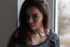 Όμορφο κορίτσι που στέκεται κοντά σε ένα παράθυρο Στοκ εικόνα με δικαίωμα ελεύθερης χρήσης