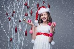 Όμορφο κορίτσι που στέκεται κοντά στο δέντρο με τις διακοσμήσεις Χριστουγέννων στοκ φωτογραφία