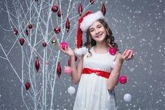 Όμορφο κορίτσι που στέκεται κοντά στο δέντρο με τις διακοσμήσεις Χριστουγέννων στοκ φωτογραφία με δικαίωμα ελεύθερης χρήσης