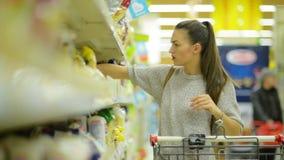 Όμορφο κορίτσι που στέκεται κοντά στο ράφι με τα ζυμαρικά και που κοιτάζει προσεκτικά σε κάθε προϊόν στο χέρι της απόθεμα βίντεο