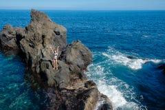Όμορφο κορίτσι που στηρίζεται στη φυσική ωκεάνια πισίνα στοκ εικόνα με δικαίωμα ελεύθερης χρήσης