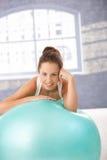 Όμορφο κορίτσι που στηρίζεται στο fitball μετά από το workout Στοκ Εικόνες