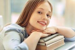 Όμορφο κορίτσι που στηρίζεται το πηγούνι της στο σωρό των βιβλίων Στοκ Εικόνες