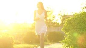 Όμορφο κορίτσι που τρέχει έχοντας τη διασκέδαση την πράσινη θερινή ημέρα πάρκων στο ηλιοβασίλεμα ήλιων Ελευθερία, υγεία, έννοια ε απόθεμα βίντεο