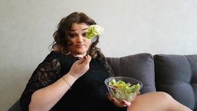 Όμορφο κορίτσι που τρώει τη σαλάτα το πεινασμένο ορεκτικό συγκίνησης αποστροφής amazement καναπέδων βιταμινών φιλμ μικρού μήκους