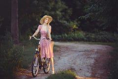 Όμορφο κορίτσι που φορά ένα συμπαθητικό ρόδινο φόρεμα που έχει τη διασκέδαση σε ένα πάρκο με ένα ποδήλατο που κρατά ένα όμορφο κα Στοκ Εικόνα